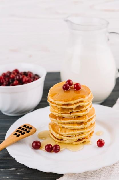 Délicieuses crêpes au miel et aux baies de cassis sur une plaque blanche Photo gratuit