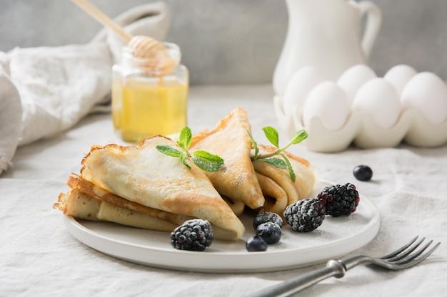 Délicieuses crêpes russes traditionnelles, miel. Photo Premium