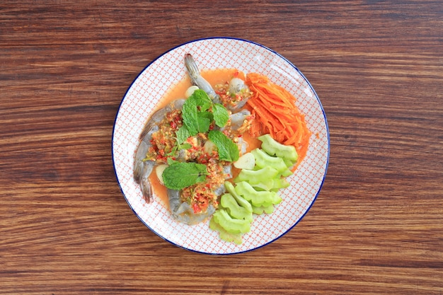 Délicieuses crevettes crues dans une sauce aux fruits de mer au piment avec une feuille de menthe et des légumes dans une assiette Photo Premium