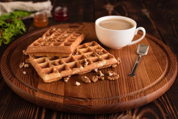 Délicieuses gaufrettes fraîches de vienne, confiture et tasse de café sur un fond en bois foncé Photo Premium
