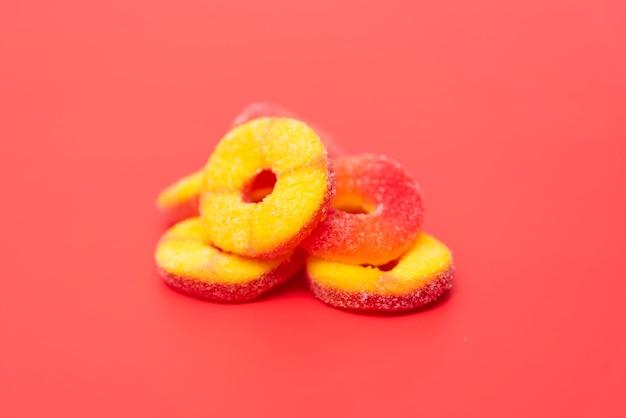 Délicieuses gelées de fruits sur fond rouge Photo gratuit
