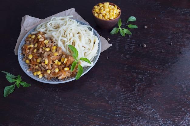 Délicieuses nouilles aux légumes dans une grande assiette. grains de maïs à la banque. Photo Premium