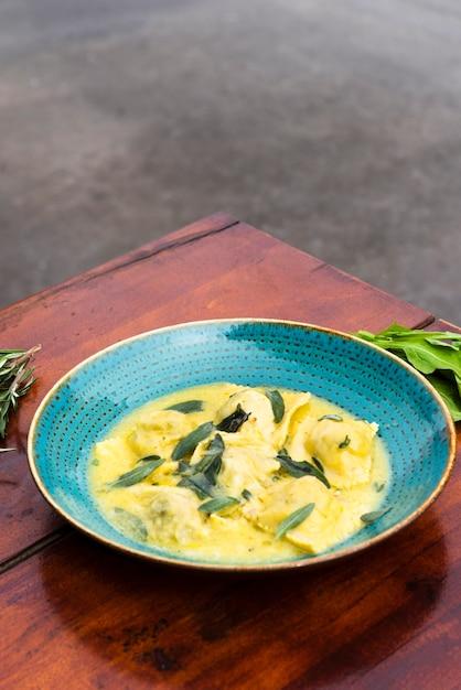 Délicieuses pâtes aux raviolis garnies de parmesan et de basilic dans une assiette sur une table en bois Photo gratuit