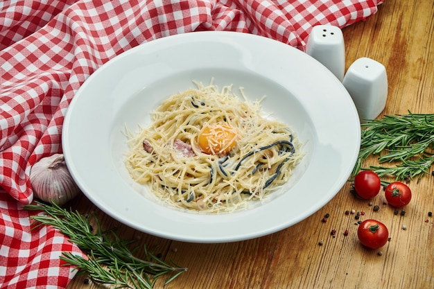 Délicieuses Pâtes Carbonara Maison Avec Bacon, Jaune D'oeuf Et Parmesan Dans Un Bol Blanc Sur Bois. Photo Premium