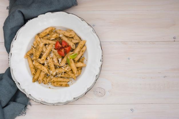 Délicieuses penne au fromage râpé et à la tomate sur une plaque blanche en céramique sur le bureau en bois Photo gratuit