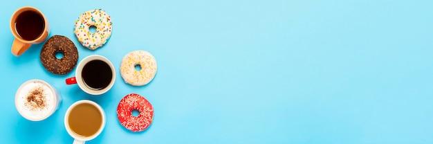 Délicieux Beignets Et Tasses Avec Boissons Chaudes, Café, Cappuccino, Thé Sur Une Surface Bleue. Concept De Bonbons, Boulangerie, Pâtisseries, Café, Réunion, Amis, équipe Amicale. Mise à Plat, Vue De Dessus Photo Premium