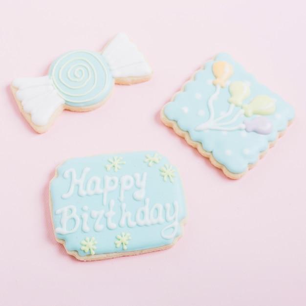 Délicieux biscuits décorés avec différentes formes sur fond rose Photo gratuit