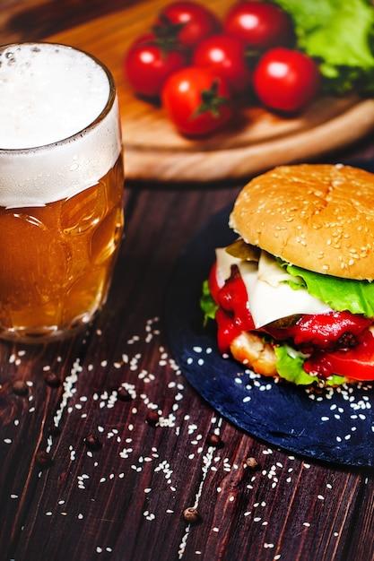 Un délicieux burger de bœuf avec de la laitue et des pommes de terre, un verre de bière servi sur une planche à découper en pierre. sombre Photo Premium