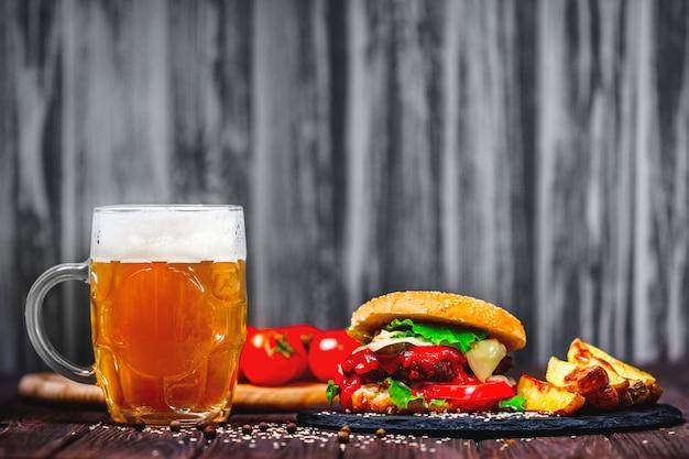 Un délicieux burger de bœuf avec de la laitue et des pommes de terre, un verre de bière servi sur une planche à découper en pierre. Photo Premium
