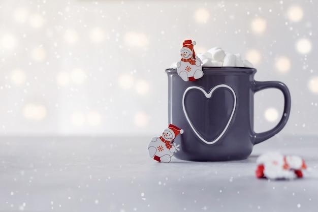 Délicieux chocolat chaud avec bonhommes de neige à la guimauve et un peu sur fond de pierre grise Photo Premium