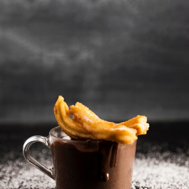 Délicieux chocolat fondu dans une tasse avec des churros Photo gratuit