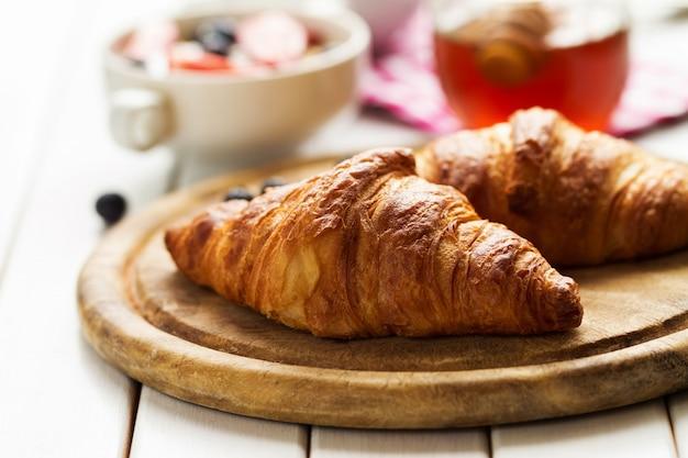 Des délicieux croissants savoureux sur une planche de bois. petit-déjeuner continental traditionnel. granola aux fruits et au miel sur le fond. Photo gratuit