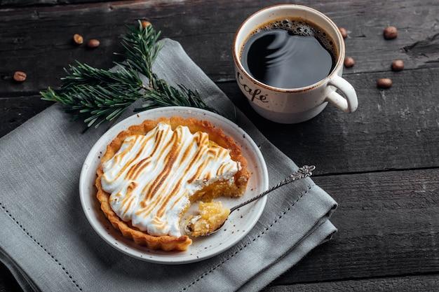 Délicieux Dessert De Noël. Tarte Au Citron Avec Meringue Et Tasse De Café Sur Une Table En Bois Sombre. Décoration De Vacances De Noël Photo Premium