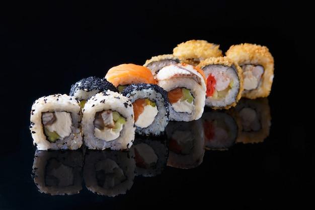 Délicieux ensemble de sushi roll avec du poisson sur un fond noir avec reflet menu et restaurant Photo Premium