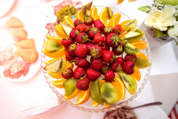 Délicieux fruits en assiette sur une table de fête. Photo Premium