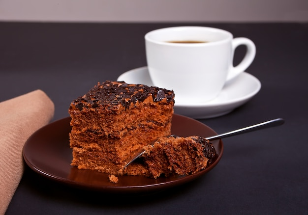 Délicieux gâteau au chocolat sur la plaque brune avec une tasse de café sur la table noire Photo Premium