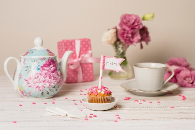 Délicieux gâteau avec drapeau décoratif avec titre de maman près de théière, fleurs et coupe Photo gratuit