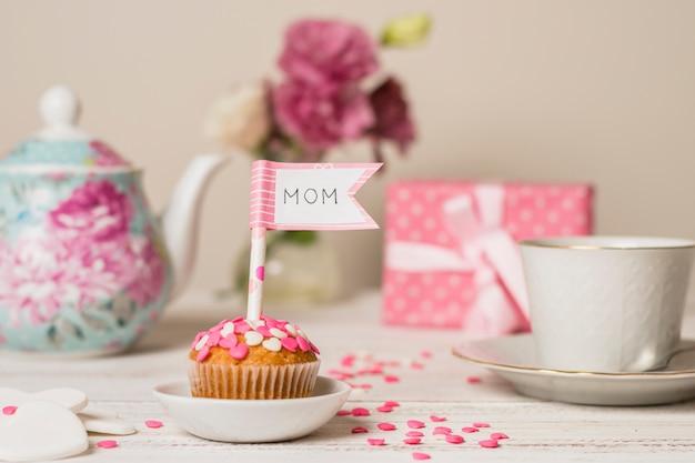 Délicieux gâteau avec drapeau décoratif avec titre de maman près de théière et tasse Photo gratuit