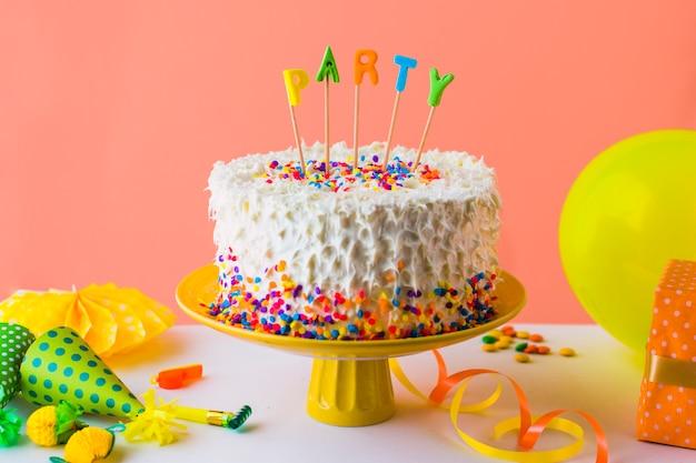 Délicieux gâteau de fête avec accessoires sur le dessus de table blanc Photo gratuit