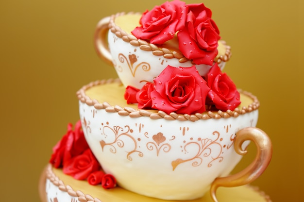 Délicieux gâteau de mariage original décoré de fleurs rouges Photo Premium