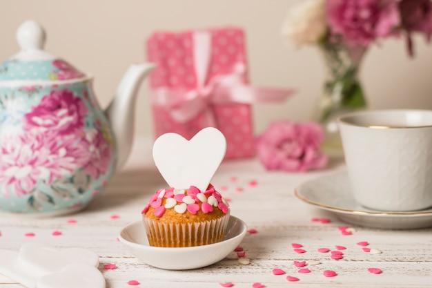 Délicieux gâteau près de la théière, du cadeau et de la tasse Photo gratuit