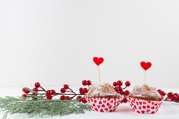 Délicieux gâteaux avec des cœurs sur des baguettes près de brindilles Photo gratuit