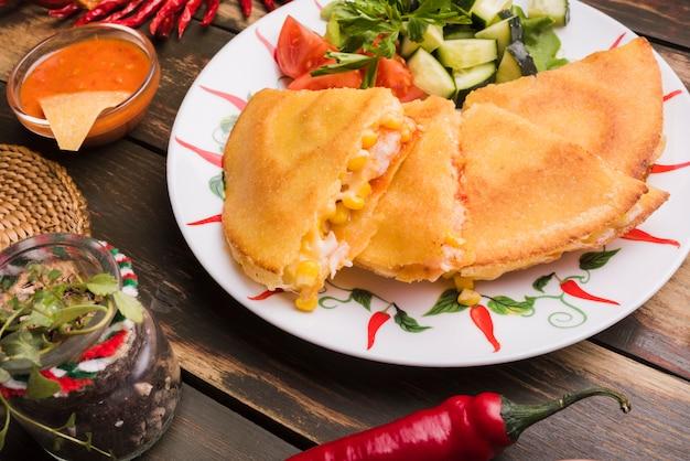 Délicieux gâteaux près de la salade de légumes sur l'assiette parmi les nachos avec sauce et piment Photo gratuit