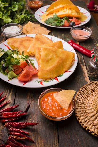 De délicieux gâteaux près de salades de légumes sur des assiettes parmi des nachos avec des sauces Photo gratuit
