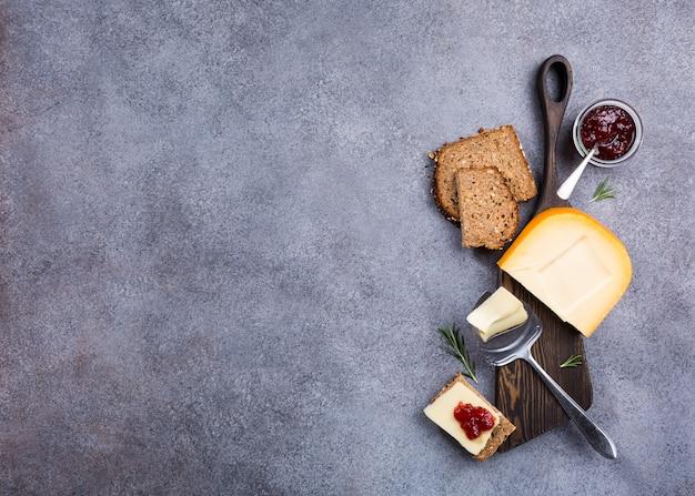 Délicieux gouda hollandais avec tranches de fromage, pain multigrain, confiture de fraises Photo Premium