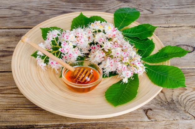 Délicieux miel de châtaigne en verre sur une surface en bois. Photo Premium