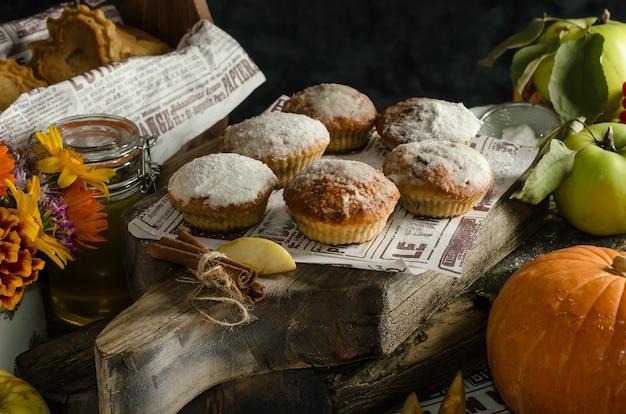 De Délicieux Muffins Maison Aux Pommes Et à La Citrouille Saupoudrés De Sucre Glace Sur Une Surface Sombre, Des Pâtisseries D'automne Pour Halloween Photo Premium