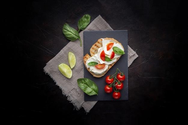 Délicieux Pain Au Fromage Et Tomate Sur Fond Noir Photo gratuit