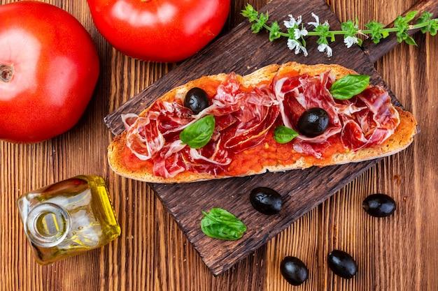 Délicieux pain grillé à la tomate naturelle, à l'huile d'olive extra vierge, au jambon ibérique, aux olives noires et aux feuilles de basilic. Photo Premium