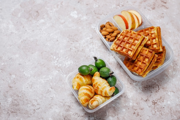 Délicieux petit déjeuner avec amandes, tranches de pommes rouges, gaufres, croissants sur boîte à lunch en plastique à la lumière Photo gratuit
