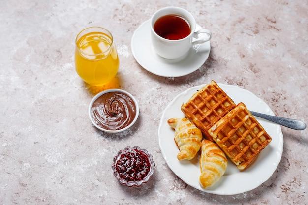 Délicieux petit déjeuner avec café, jus d'orange, gaufres, croissants, confiture, pâte de noix à la lumière, vue de dessus Photo gratuit