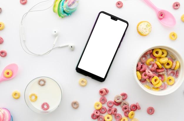 Délicieux petit déjeuner avec des céréales et un téléphone portable sur la table Photo gratuit