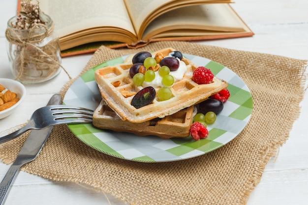Délicieux Petit-déjeuner Avec Des Gaufres Et Des Fruits Près D'un Livre Photo gratuit