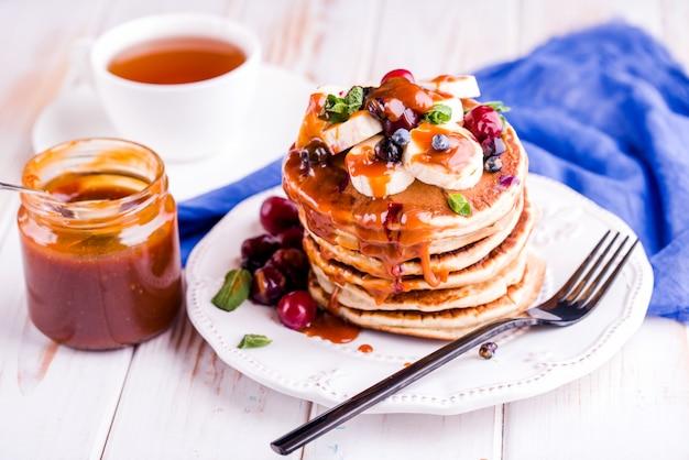 Délicieux Petit-déjeuner Sain Et Copieux Sur Le Tableau Blanc. Crêpes Aux Fruits, Jus D'orange. Haut Photo Premium