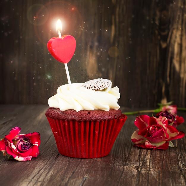 Délicieux petit gâteau de velours rouge avec une bougie allumée Photo Premium