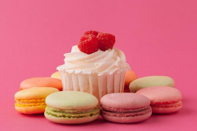 Délicieux petits gâteaux sur fond rose clair Photo Premium