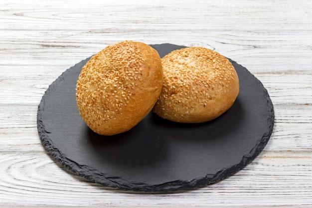 De délicieux petits pains frais aux graines de sésame sur une ardoise. vue de dessus Photo Premium