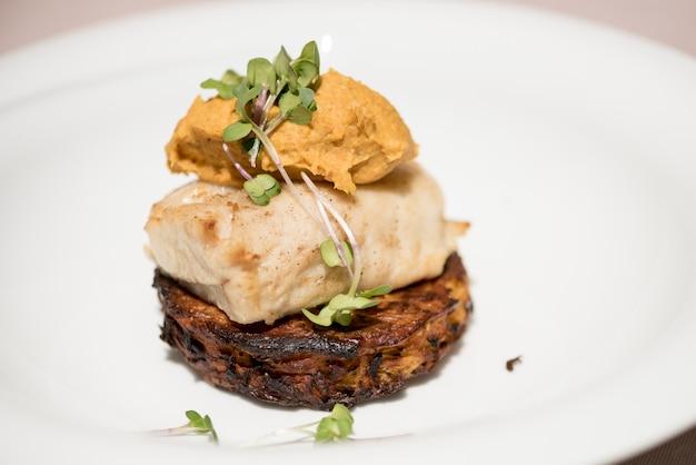De délicieux poissons blancs servis sur des courgettes frites, avec une purée de patate douce et une sauce pourpre Photo Premium