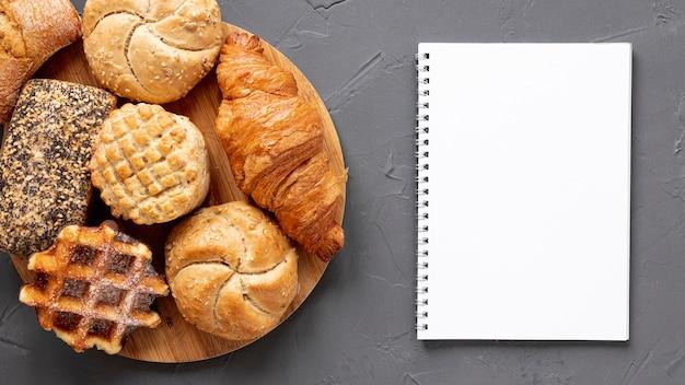 Délicieux produits de pâtisserie et un cahier Photo gratuit