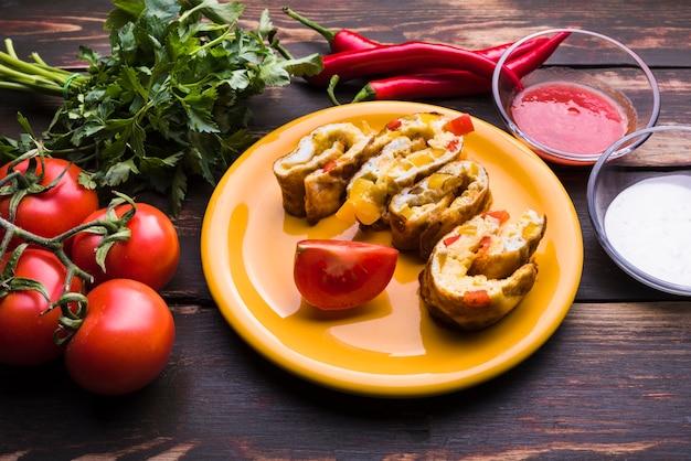 Délicieux rouleau sur assiette parmi les légumes et les sauces Photo gratuit