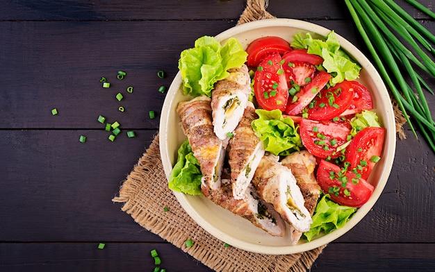 Délicieux rouleaux de poulet farcis au fromage et aux épinards enveloppés dans des lardons de lard, vue de dessus Photo Premium
