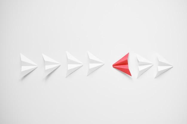 Démarquez-vous Le Concept. Avion En Papier Rouge Se Démarquant De La Ligne Des Blancs Et Se Battant Pour être Contre Tous. Photo Premium