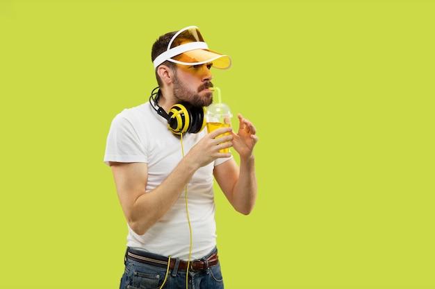 Demi-longueur Gros Plan Portrait De Jeune Homme En Chemise Sur L'espace Jaune. Modèle Masculin Avec Un Casque Et Une Boisson. Photo gratuit