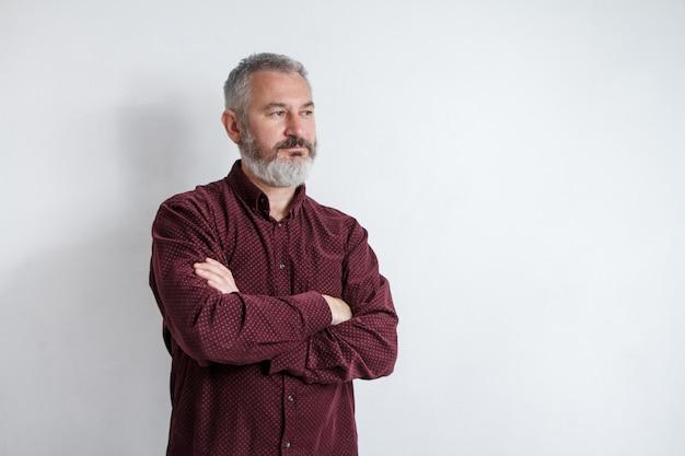 Demi-longueur portrait d'un homme sérieux barbu aux cheveux gris dans une chemise bordeaux sur fond blanc Photo Premium