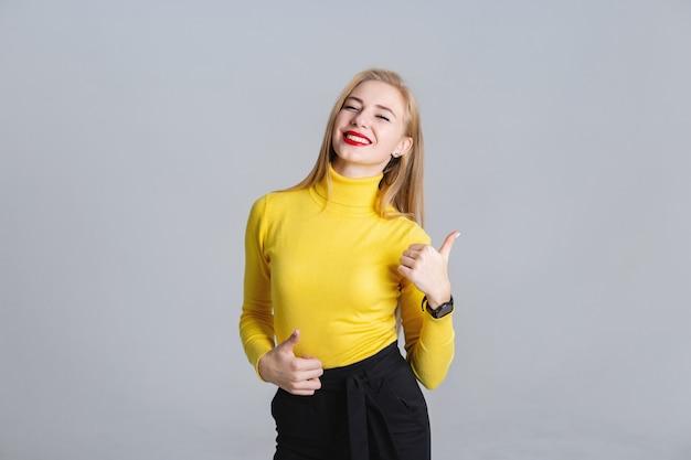 Demi-longueur portrait de joyeuse fille montrant le pouce vers le haut Photo Premium