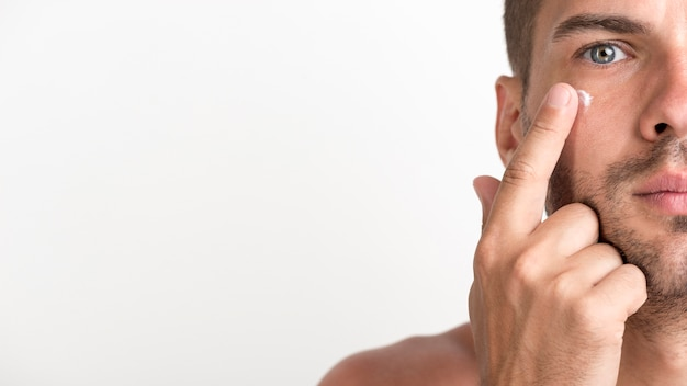 Demi visage de jeune homme torse nu, appliquant la crème sur son visage contre un fond blanc Photo gratuit